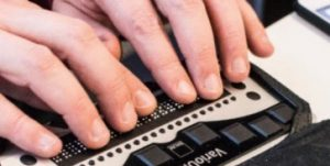 Fingers on keyboard of braille display