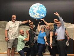 COSB Board pretend to 'hold up' a background image of the Earth