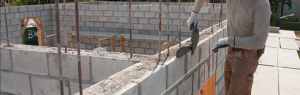 man with trowel building a concrete block wall